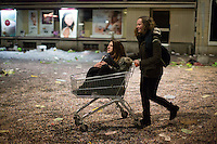 A woman pushes another in a shopping cart along a confetti-covered main road in the old town of Basel as the Carnival of Basel, or Fasnacht, comes to an end. Basel, Switzerland. Feb. 26, 2015.