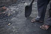 Rio Negro, Amazonas State, Brazil. The blackened feet of a charcoal worker, shovel.