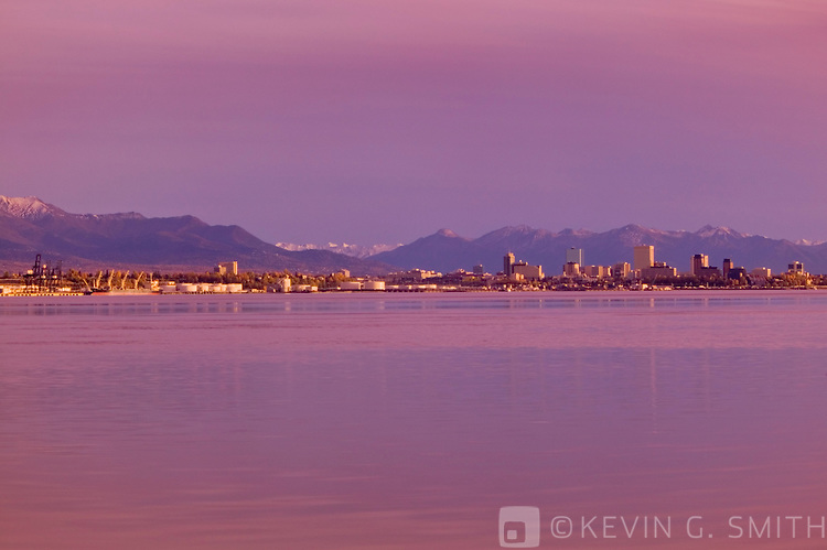 View of downtown Anchorage skyline and the port from across Knik arm, shot from the port at Point Mckensie. Kenai mountains in background. Fall, sunset, Anchorage Alaska.