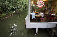 Tourists in a coffee shop suspended above West Lake in Hangzhou, one of the most visited tourists sites in China. Zhejiang Province. China. 2010
