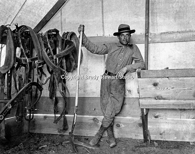 Products: Pitch Folk and Horse Harnesses<br /> <br /> Brady Stewart baling hay on the Idaho estate.  Brady Stewart and three friends went to Idaho on a lark from 1909 thru early 1912. As part of the Mondell Homestead Act, they received a land grant of 160 acres north of the Snake River.  For 2 ½  years, Brady Stewart photographed the adventures of farming along with the spectacular landscapes.