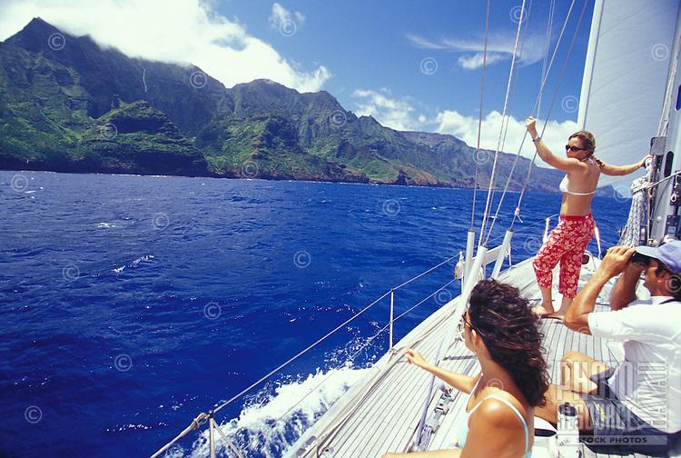 Woman looking at waterfall on Kauai's Na Pali Coast from deck of sailing yacht
