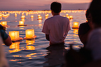 On the evening of Memorial Day, spectators watch lanterns floating on the ocean during the 15th Annual Lantern Floating Ceremony at Ala Moana Beach Park, Honolulu, O'ahu.