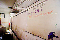 A homework assignment on the dry erase board at Edward Hynes Elementary and Middle School in the city of New Orleans shows the last date class was held, on December 10, 2005.