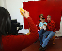 Newly adoptive parents,  have a official portraits taken with their newly adopted baby daughter by government officials. The babies belong to a group of Canadian nationals going through the adoption procedure in Changsha, Hunan, China.