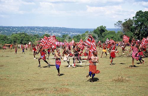 Lolgorian, Kenya. Siria Maasai; Eunoto ceremony; moran carrying flags running through the Manyatta.