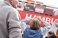 Touristen betrachten im Hamburger Hafen von einer Barkasse aus die Vorbeifahrt eines Containerschiffes.<br /> 12.4.2015, Hamburg<br /> Copyright: Christian-Ditsch.de<br /> [Inhaltsveraendernde Manipulation des Fotos nur nach ausdruecklicher Genehmigung des Fotografen. Vereinbarungen ueber Abtretung von Persoenlichkeitsrechten/Model Release der abgebildeten Person/Personen liegen nicht vor. NO MODEL RELEASE! Nur fuer Redaktionelle Zwecke. Don't publish without copyright Christian-Ditsch.de, Veroeffentlichung nur mit Fotografennennung, sowie gegen Honorar, MwSt. und Beleg. Konto: I N G - D i B a, IBAN DE58500105175400192269, BIC INGDDEFFXXX, Kontakt: post@christian-ditsch.de<br /> Bei der Bearbeitung der Dateiinformationen darf die Urheberkennzeichnung in den EXIF- und  IPTC-Daten nicht entfernt werden, diese sind in digitalen Medien nach §95c UrhG rechtlich geschuetzt. Der Urhebervermerk wird gemaess §13 UrhG verlangt.]