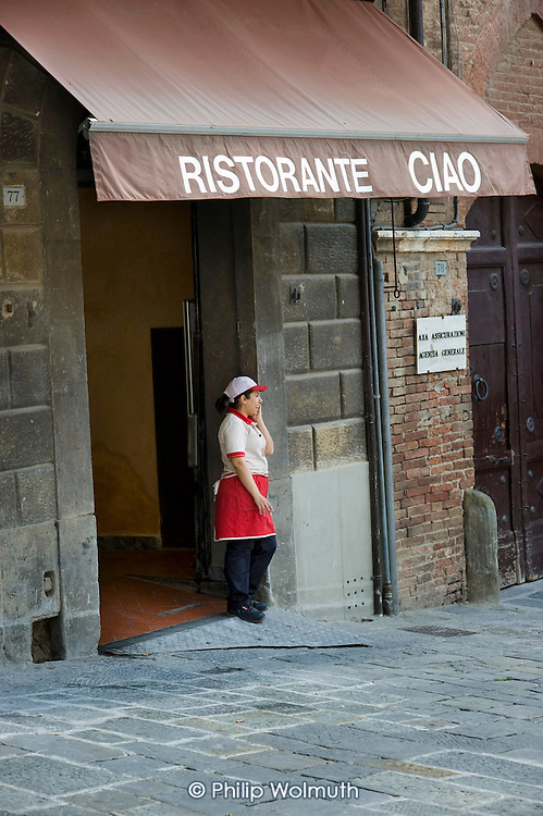 A catering worker talks on a mobile phone outside a restaurant in Siena during a cigarette break.