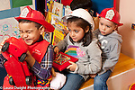Education Preschool 3-4 year olds pretend play group of two boys and a girl wearing dressup hats traveling in vehicle together