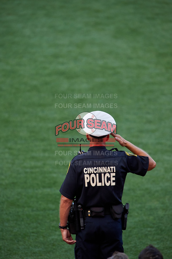 Cincinnati Police Officer salutes during the national anthem before the MLB Home Run Derby on July 13, 2015 at Great American Ball Park in Cincinnati, Ohio.  (Mike Janes/Four Seam Images)