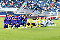 KANSAS CITY, KS - SEPTEMBER 23: Orlando players stand with face masks and the officials and Sporting KC players kneel prior to the kick off during a game between Orlando City SC and Sporting Kansas City at Children's Mercy Park on September 23, 2020 in Kansas City, Kansas.