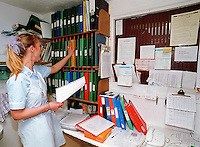 Residential care home nurse checking through residents medical files. This image may only be used to portray the subject in a positive manner..©shoutpictures.com..john@shoutpictures.com