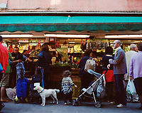 A bustling fruit and vegetable stall in a Venice market.