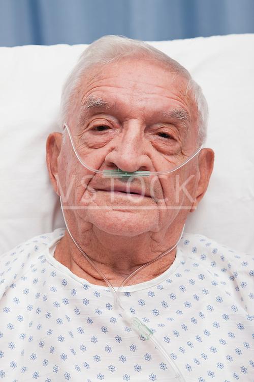 USA, Illinois, Metamora, Portrait of senior man with ear nasal cannula lying in hospital bed