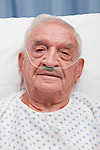 USA, Illinois, Metamora, Portrait of senior man with ear nasal cannula lying in hospital bed
