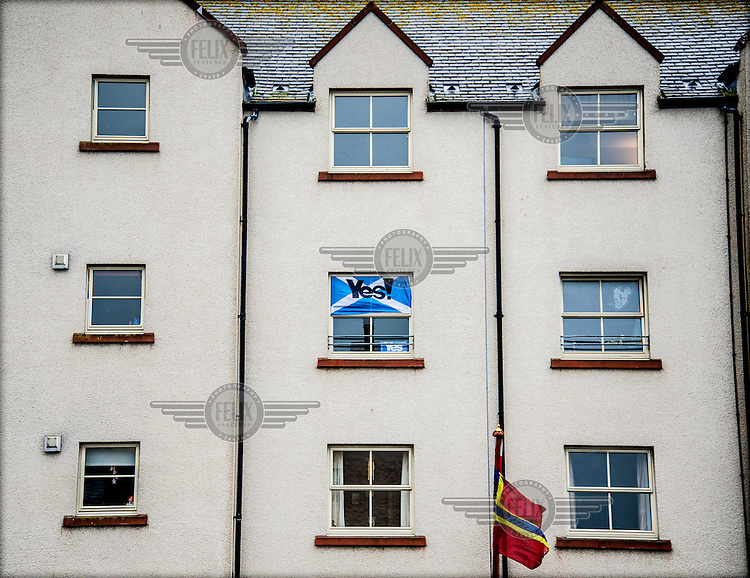 A Scottish flag with the word 'Yes!' is displayed in a window on Harbour Street in Kirkwall, the capital of the Orkney Islands. The 'Yes' campaign is calling for Scottish people to vote in favour of seceding from the United Kingdom and becoming an independent country in a referendum held on 18 September 2014.