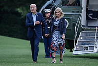 United States President Joe Biden and first lady Jill Biden hold hands as they walk off of Marine One on the South Lawn of the White House in Washington, DC on Sunday, July 18, 2021. The Bidens spent the weekend at Camp David, the presidential retreat near Thurmont, Maryland.  <br /> CAP/MPI/RS<br /> ©RS/MPI/Capital Pictures