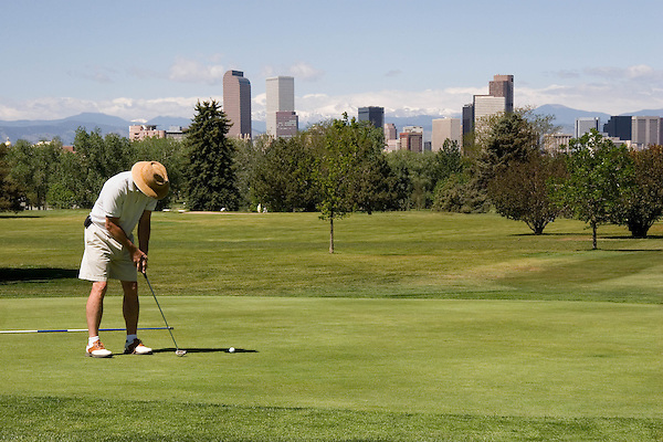 Man putting in City Park Golf Course; Denver; Colorado. .  John offers private photo tours in Denver, Boulder and throughout Colorado. Year-round Colorado photo tours.