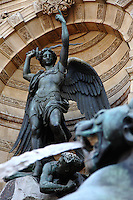 An artistic view of the fountain of Saint Michel in Paris, with the head of one of the dragons in the foreground and the spurt of water which protects the victim from the sward of the angel.
