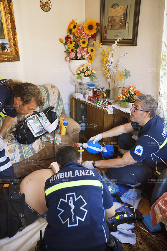 Switzerland. Canton Ticino. Lugano. The emergency doctor Daniele Speciale (R) is working with two paramedics. A senior man is lying down unconscious due to a heart attack. Myocardial infarction (MI), commonly known as a heart attack, occurs when blood flow decreases or stops to a part of the heart, causing damage to the heart muscle. 45 minutes after arrival, with no restart of heart beats, the doctor Daniele Speciale had to declared the man dead. Paramedics team wears blue uniforms and work for theCroce Verde Lugano. The man (L) and the woman (C) are professional certified nurses. On the couch, a monitor is used to controls vital functions, such as electrocardiogram, blood pressure's measurement, respiratory rate and pulse oximetry (oxygen saturation).TheCroce Verde Lugano is a private organization which ensure health safety by addressing different emergencies services and rescue services. 13.01.2018 © 2018 Didier Ruef