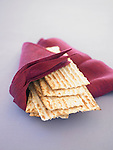 Stack of matzah (unleavened bread), wrapped in a maroon cloth napkin, on a purple background