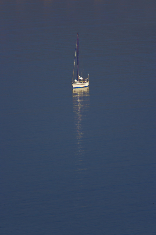 Sailboat on calm water of Drakes Bay. Point Reyes National Seashore. California