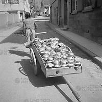 Mädchen zieht Handkarren mit Milchkannen, Deutschland 1930er Jahre. Girl pulling push cart with milk cans, Germany 1930s.