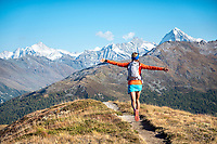 Running joyfully on the Via Valais, a multi-day trail running tour connecting Verbier with Zermatt, Switzerland. A woman runs towards the distant big mountains, where she is headed as part of the tour.