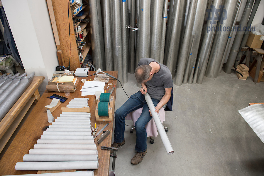 """July 13, 2016; McLeod and Greg Bahnsen might work on dozens of pipes in a single session. Then again, a 16-foot pipe for the organ in the Columbus, Ohio, cathedral weighed 125 pounds and simply burnishing it took a whole day. """"You can do a lot sitting in this chair,"""" McLeod quips. (Photo by Barbara Johnston/University of Notre Dame)"""