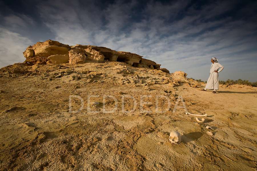 Human remains are visible in the desert sands near ancient tombs on the outskirts of Siwa Town in the Siwa Oasis, Egypt. A local, young Siwan man dressed in tradional clothing stands on the tomb site.