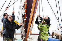 Crewmembers pull together on one of the Polynesian Voyaging canoes Hokule'a or Hikianalia, Pacific Ocean, March 2013.