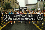 """Demonstration CND Campaign Nuclear Disarmament London to Hyde Park 1982  against the conflict in the Falklands. CND women march against war in the Falklands through streets London. Joan Ruddock Labour MP - centre in red coloured open neck shirt wearing white trousers behind the """"MPA"""" of Campaign."""