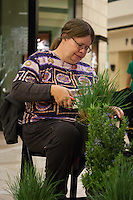 """Janis Hunter works to prepare plants (""""detail"""" them to get rid of dead leaves and shape them) at Orange Coast College's Ornamental Horticulture Club's in-progress installation at the 2012 South Coast Plaza Spring Garden Show in Costa Mesa, CA.  The theme for this year's show is """"healing gardens"""", and the OCC team is installing a """"garden for the blind,"""" which will be complete with a braille world globe and braille labels.  This picture was taken Tuesday April 25, 2012 at ~11pm, as the team was working frantically to meet their Thursday-morning deadline.  This image was taken at a high ISO using the ambient light in the dim mall, so it's noisier than my typical images (and thus I'd recommend against printing it large)."""