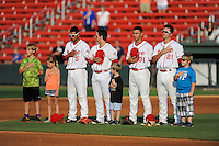 Deiner Lopez, Michael Chavis, Javier Guerra and Nick Longhi of the Greenville Drive stand for the National Anthem with youth players on Monday, June 29, 2015, at Fluor Field at the West End in Greenville, South Carolina. Greenville won, 4-2. (Tom Priddy/Four Seam Images)