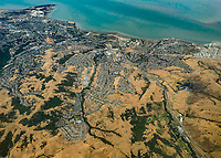 California subdivision encroaching summer-dry hills and open space by San Francisco Bay; seen from airplane to Alaska