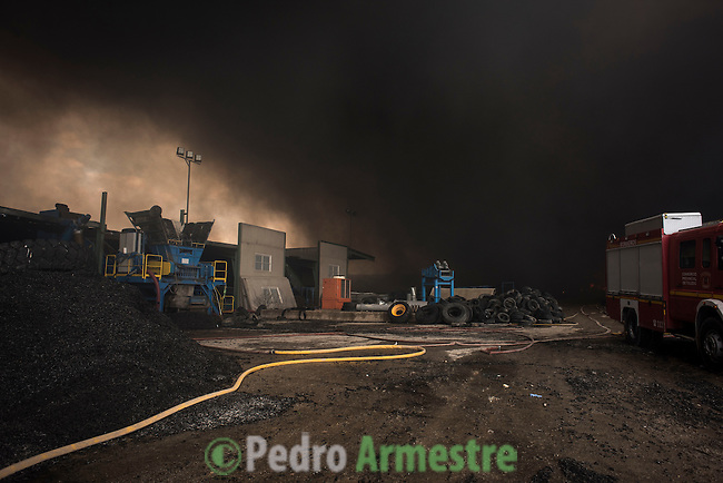 Clouds of dark smoke cover the sky as a fire truck works in an uncontrolled tyres dump near the town of Sesena, after a fire broke out early on May 13, 2016. A huge waste ground near Madrid where millions of tyres have been dumped was on fire today, releasing a thick black cloud of toxic fumes that officials worry could harm residents nearby.  © Pedro ARMESTRE