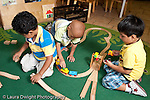 Education Preschool 3-5 year olds group of three boys playing separately with wooden train set horizontal