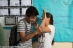 Education high school classroom scenes couple laughing and mock fighting in corridor between classes
