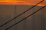 The rising sun lit up the top of northern tower of the Golden Gate Bridge as the tallest building of the San Francisco framed the scene.