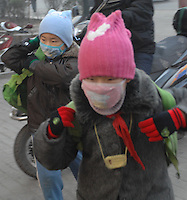 Children make their way to school wearing protective masks in Linfen, Shanxi Province, China. Linfen has been identified as one of the most polluted cities in China..30 Jan 2007