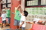 Education Preschool 3-5 year olds group of boys playing in pretend play area exuberant throwing stuffed animal toys in air horizontal