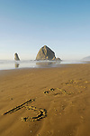 Haystack Rock at Cannon Beach with ?J loves M? written in sand; Oregon coast.
