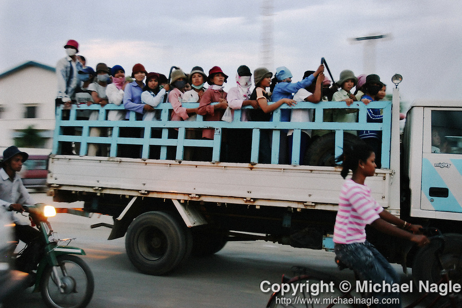 CAMBODIA  -  APRIL 19, 2005:   Garment workers leave work on Veng Sreng Street in Phnom Penh. The World Trade Organization recently abolished textile quotas and, as a result, some of the world's smallest and least developed countries like Cambodia will see their textile industries pushed out to the periphery. Moreover, in 2005, a unique agreement that grants Cambodian garments and textiles exclusive access to lucrative US markets will expire, opening up the garment industry to competition with every other manufacturing country in the world.  (PHOTOGRAPH BY MICHAEL NAGLE)