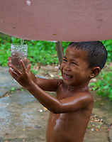 A young boy is collecting rainwater during a monsoon rain shower, Rural area near Battambang, Cambodia