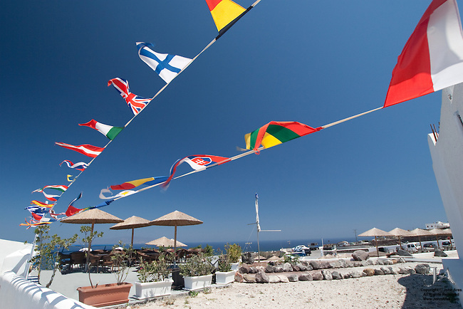 Pennants fly in the blue sky in Oia