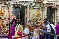 Hindu Temple Sri Vadapathira Kaliammam during Navarathiri Celebrations, Singapore.  Hindu Priest Blessing Worshipers outside Entrance to Inner Sanctuary.