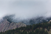 The foothills west of Boulder, a mixture of barren rock and evergreens, are blanketed by clouds and dusted with snow.