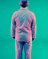 Old man in pajamas on green background<br />