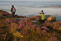 15/08/16<br /> <br /> A photographer takes shots among the heather and gritstone crags. After a chilly night in the Peak District, low cloud blankets the stunning Derbyshire countryside as the sun rises over Curbar Edge this morning ahead of a forecast week of late summer hot weather.<br /> <br /> This type of weather phenomena is known as an inversion and can occur when, for example, a warmer, less-dense air mass moves over a cooler, denser air mass. This type of inversion occurs in the vicinity of warm fronts.<br /> <br /> All Rights Reserved, F Stop Press Ltd. +44 (0)1773 550665