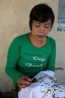Yogyakarta, Java, Indonesia.  Batik Production.  Woman Using Hot Wax to Outline a Design on a Batik Cloth.